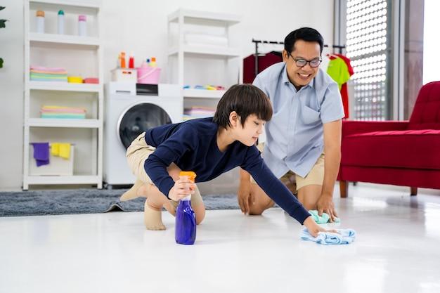 Счастливая семья убирает комнату азиатские отец и сын убирают в доме