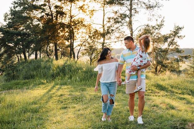 幸せな家族の概念-楽しんで、自然の中で遊んでいる父、母と子の娘。