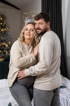幸せな家族の概念。夫はソファの近くの屋内リビングルームに立っている腹妊娠中の妻を抱きしめます白人男性と女性の妊娠と新しい生活の概念。愛とケア