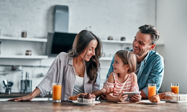 キッチンで幸せな家族のコンセプト。かわいい女の子と彼女の美しい両親は、おいしい朝食の準備をしながらスマートフォンを使用して笑っています。