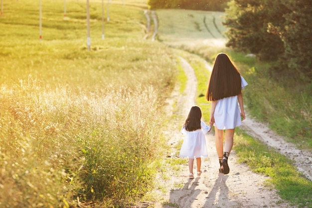 Happy family concept. mom and baby holding hands and walking in evening in rays of beautiful sunset. little daughterwalks with her mother on road. yellow field, sunset sun, summer day and evening