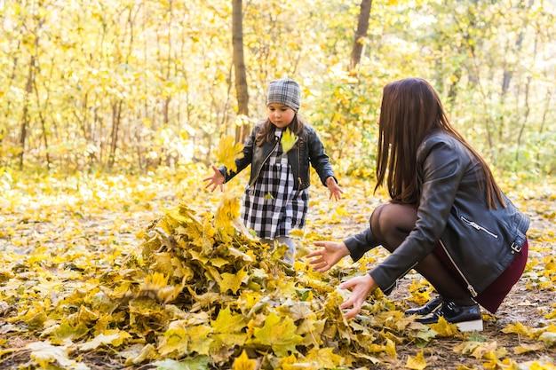 幸せな家族の概念-秋の自然の中で遊ぶ母と子の小さな娘。