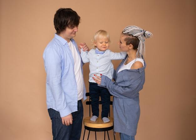 幸せな家族の概念。母と父と幼い息子がベージュの壁に隔離