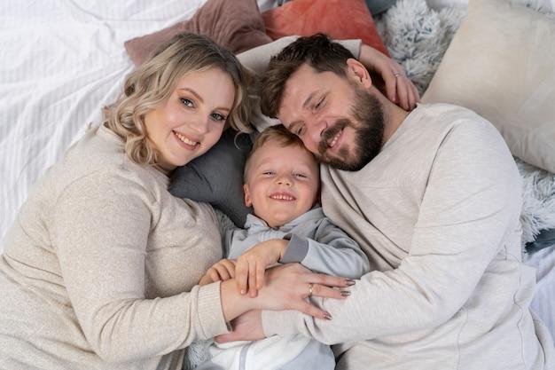 행복한 가족 개념 어머니 아버지와 작은 아들은 집에서 재미를 백인 가족 실내 임신 엄마 수염 아빠와 재미있는 어린 소년 소파에 누워