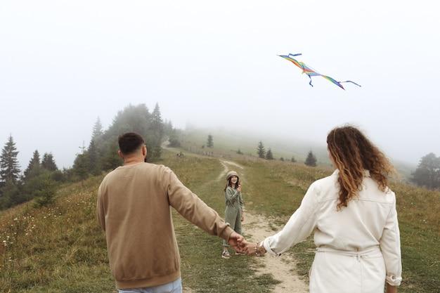 幸せな家族の概念。親子で色とりどりの凧で遊んでいます。霧の日に屋外で一緒に楽しんでいる若い母、父と小さなかわいい娘。