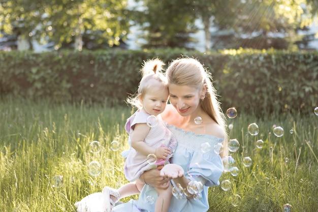 Концепция счастливой семьи с молодой матерью, играющей со своей девочкой и делая мыльный пузырь