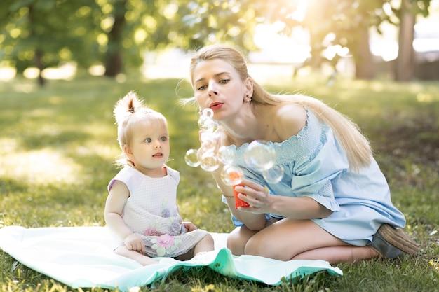 Концепция счастливой семьи с молодой матерью, играющей со своей девочкой и делая мыльные пузыри