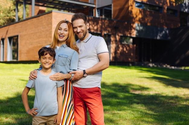 행복한 가족. 콘텐츠 사랑하는 부모가 웃고 아들과 함께 서 있습니다.