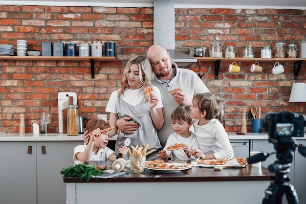 Happy family cook some food and pizza together and streaming their successes on tv. preschool boys and their parents.