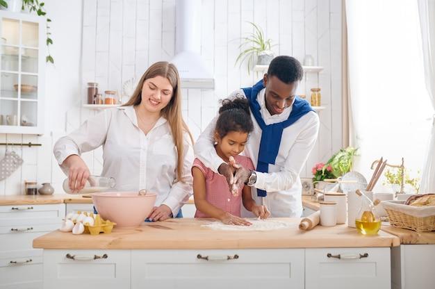キッチンで朝食にケーキを調理する幸せな家族。母、父と娘は朝に生地を準備します、良い関係