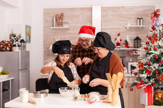 Happy family cooking homemade gingerbread dessert making traditional dough