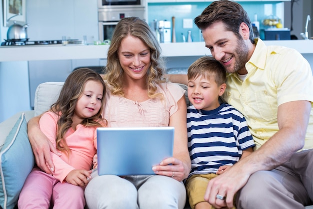 Happy family on the couch together using tablet