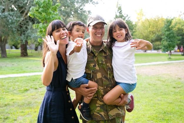 幸せな家族のカップルと公園でポーズをとる2人の子供。子供たちを腕に抱き、妻が子供たちを抱き締めて手を振っている軍人。ミディアムショット。家族の再会または帰国の概念