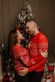 飾られたクリスマスツリーと花輪で新年とクリスマスを祝う幸せな家族のカップル