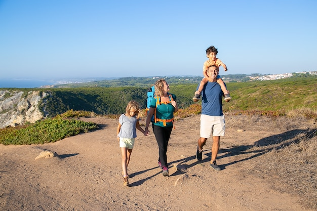 Happy family couple and children  hiking in countryside, walking on path. excited boy riding on dads neck. full length. nature and recreation concept