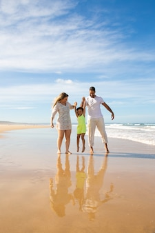 Happy family couple and little girl enjoying walking and activities on beach, kid holding parents hands, jumping and hanging