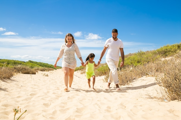 Happy family couple and little kid in summer clothes walking white along sand path, girl holding parents hands