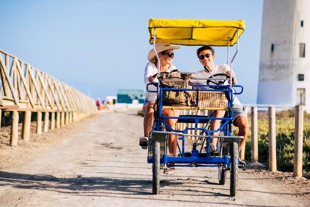 幸せな家族のカップルの母と10代の息子はたくさん笑って屋外のレジャー活動で車の車のバイクで一緒に楽しんでいます