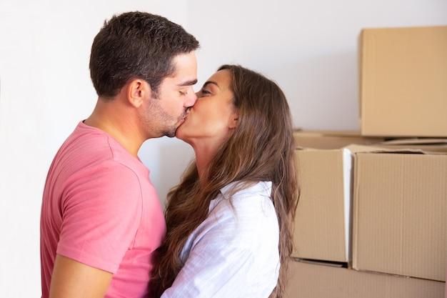 Coppia famiglia felice che entra nella nuova casa, in piedi vicino a scatole di cartone e si baciano