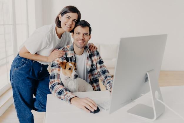 Happy family couple pose near computer monitor