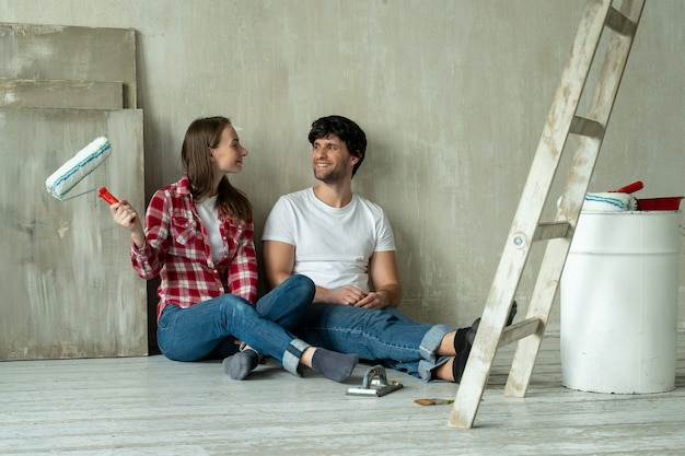 Счастливая семейная пара расслабляется после рисования молодой пары, лежащей на полу нового дома и общающейся друг с другом