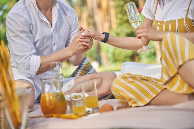 차가운 와인과 오렌지 레모네이드와 함께 시골에서 쉬고 행복한 가족 커플