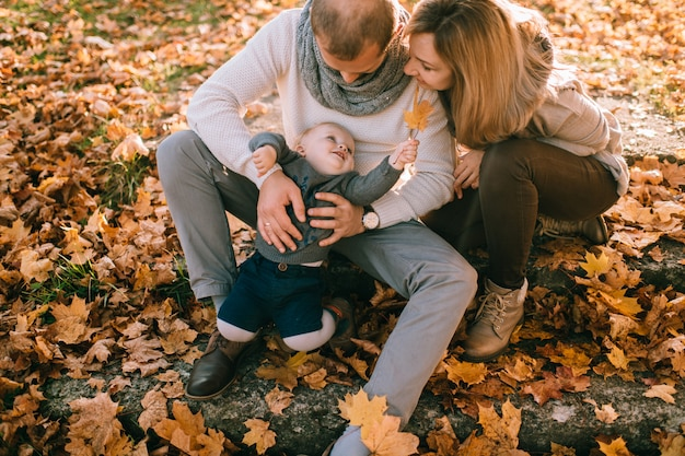 Happy family couple sitting on stairs covered by autumn leaves and holding their beautiful child