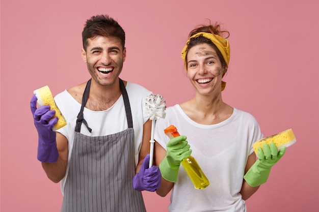 Happy family couple standing close to each other holding sponges, detergent and brush isolated