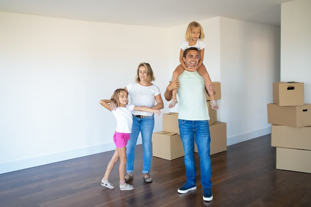 Happy family couple and two kids looking over their new apartment, standing in empty room with stacks of boxes