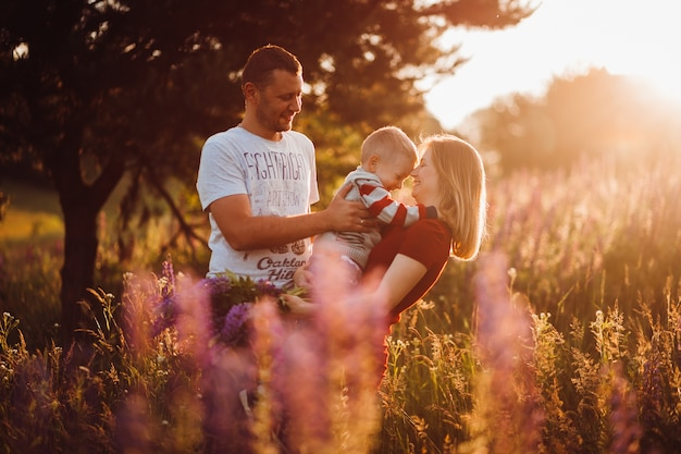 Happy family couple with little son pose on the field of lavander