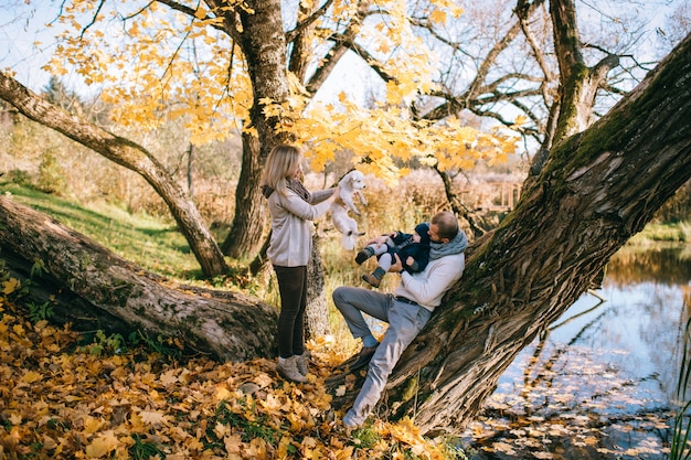 Happy family couple with their little child and puppy in autumn park in sunny day.