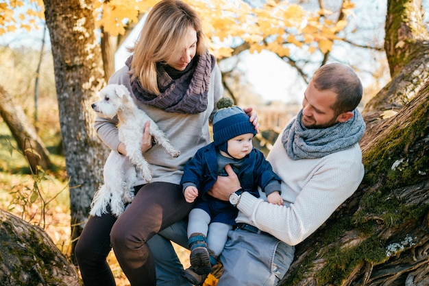 Happy family couple with their little child  and puppy spending time in autumn park.