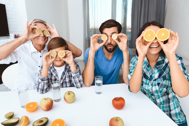 Happy family covers eyes with fruit, sitting at dinner table