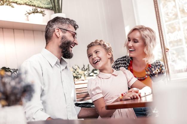행복한 가족. 카페에서 테이블에 앉아있는 동안 그녀의 아빠를보고 귀여운 즐거운 소녀