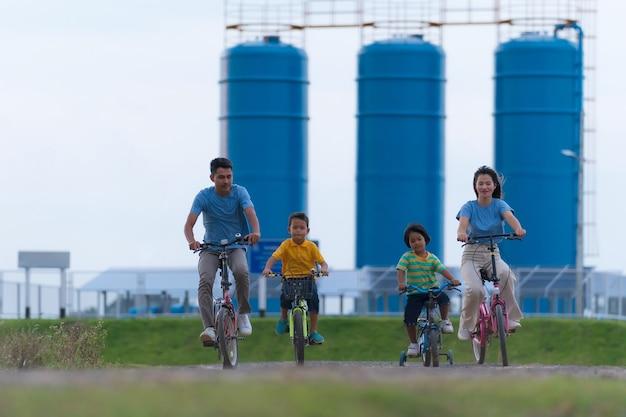 야외에서 자전거를 타는 행복한 가족, 아이들이 있는 활동적인 부모는 재미, 가족 스포츠 및 피트니스, 휴가, 시골에서 휴식을 취합니다.