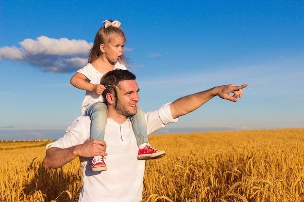 幸せな家族。日当たりの良い夏の日に父と娘が彼の肩に座って麦畑の真ん中に立つ