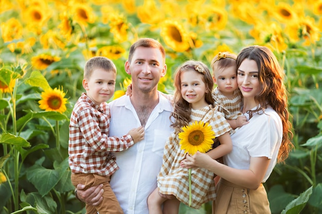 Happy family, dad, daughter and son have fun, play among blooming sunflowers in the fresh air