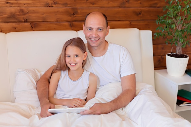 Happy family, dad and daughter talking on the tablet at home in bed. distance learning.