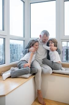 幸せな家族。彼のkdsを抱き締めて幸せそうに見えるお父さん