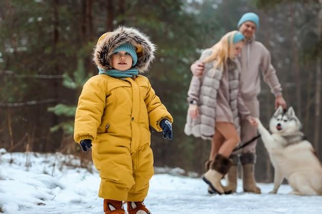 Счастливая семья, папа, мама и малыш на зимней прогулке в лесу