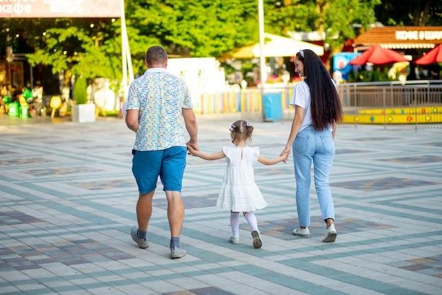 여름 휴가철 놀이공원에서 행복한 가족 아빠, 엄마, 딸 소녀는 함께 시간을 보내라고 말했습니다.