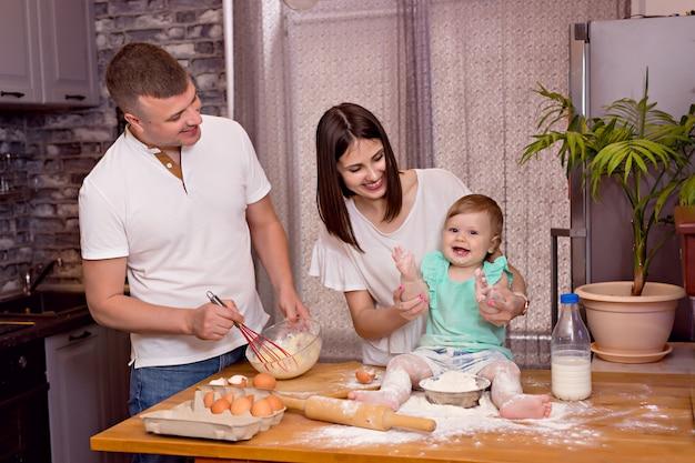 幸せな家族、お父さん、お母さん、娘が台所で遊んで、料理をしたり、生地をこねてクッキーを焼いたりします。