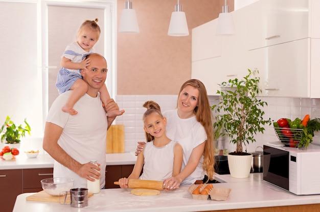 幸せな家族、お父さん、お母さん、娘たちがキッチンで料理をし、生地をこねてクッキーを焼きます。