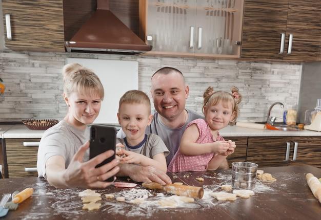 Счастливая семья, папа, мама и двое детей делают селфи на кухне во время приготовления печенья. готовим вместе счастливые семейные отношения