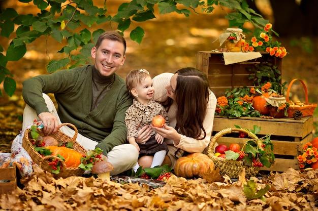 호박과 사과와 함께 가을 피크닉에서 행복한 가족 아빠, 엄마, 아기 딸