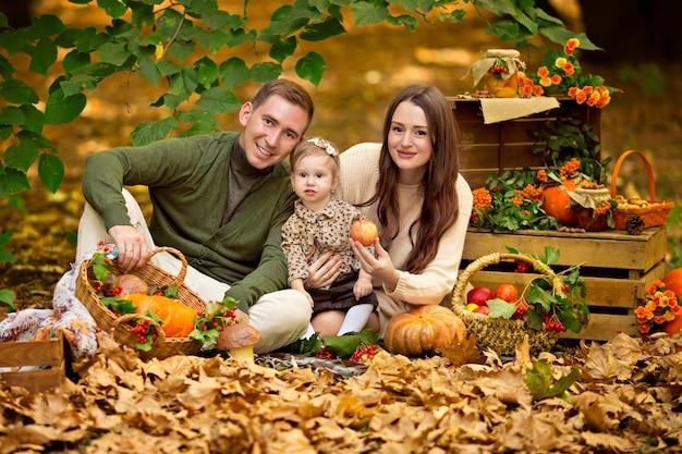 カボチャとリンゴと秋のピクニックで幸せな家族のお父さん、お母さん、赤ん坊の娘