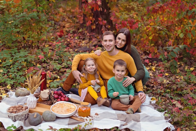 Happy family, dad, mom, little son, daughter at an autumn picnic with pie, pumpkin, tea