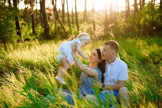 幸せな家族のお父さん、バックライトで美しい感情的な夕日を見ているフィールドで新鮮な空気で遊んでいるお母さん