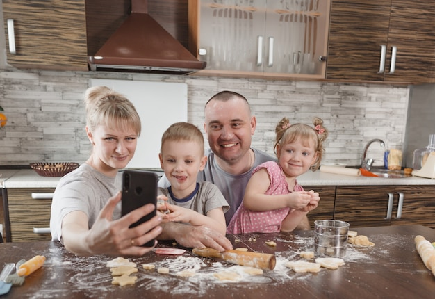 Happy family dad mom and two kids take selfies in the kitchen while making cookies. cooking together happy family relationships