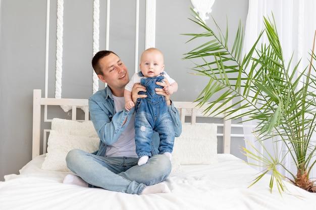 행복한 가족, 아빠가 침대 개념 또는 행복한 아버지에 집에서 아기와 함께 연주